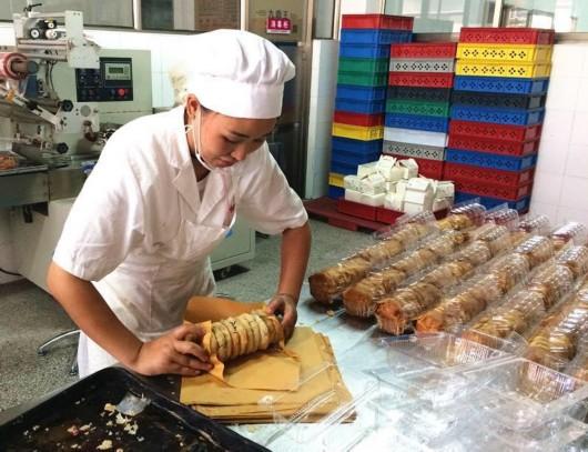 工作人员正在用纸包装装亭林月饼.彭晓华摄-为一盒鲜肉月饼 上海人